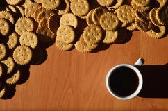 Background image of a small white cup of coffee and classic salty cracker on a brown wooden table with copyspac. E Stock Image
