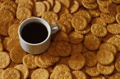 Background image of a small white cup of coffee and classic salty cracker on a brown wooden table with copyspac. E Stock Photo