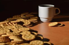 Background image of a small white cup of coffee and classic salty cracker on a brown wooden table with copyspac. E Royalty Free Stock Photos