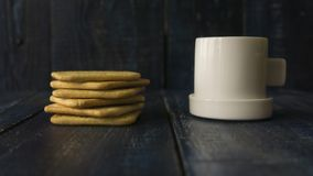 Background image of a small white cup of coffee and classic salty cracker on a dark wooden table with copyspace Royalty Free Stock Photos
