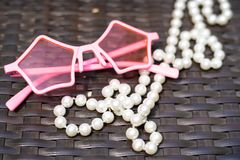 Background image of sunglasses and white pearl beads on wooden royalty free stock photos