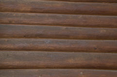 The background image of a wall made of wooden logs brown Royalty Free Stock Photo