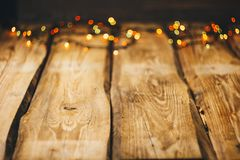 Background image. wallpapers on the desktop in the New Year style. Wooden photo background with garlands and bokeh on black. stock photos