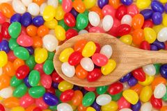 Background of jelly beans with wooden spoon holding candy too. Many brightly colored jelly beans in a rainbow of colors. Popular candy for Easter. wooden spoon Royalty Free Stock Photo