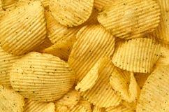 Background of juicy corrugated potato chips close-up stock photo