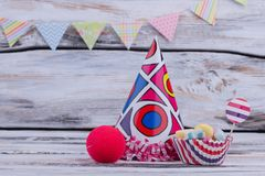 Background with kids Birthday party items. Party hat, sweeets and clown sponge nose on wooden background. Childrens Birthday supplies stock photography