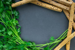 Background for kithen. Parsley and bread sticks on black background for design Stock Image
