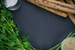 Background for kithen. Parsley and bread sticks on black background for design Royalty Free Stock Image