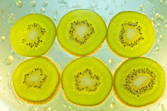 Background of kiwi  in water with bubbles Royalty Free Stock Photos
