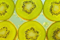 Background of kiwi in water with bubbles Stock Photos