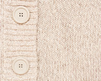 Background with knitted with buttons. Abstract beige background with a knitted fabric Stock Images