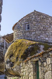 Background landscape with an unusual stone house from a huge boulder wall in the village of Monsanto Stock Image
