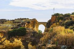 Background landscape view of an arched bridge between rocks on one of the beaches of Lagos Stock Images