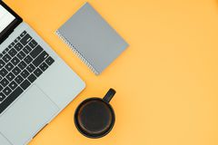 Background. Laptop, notebook and cup with coffee on a yellow background, top view, workplace royalty free stock images