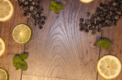 Background with lemon, lime, blueberry and mint. On wooden background Royalty Free Stock Photos