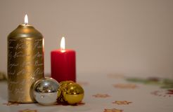 Background of lit candles with Christmas balls on a tablecloth stock images