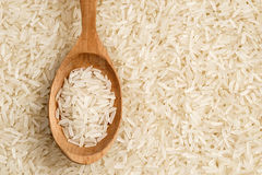 Background of long parboiled rice and wooden spoon with rice Stock Photo