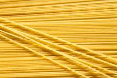 Background of long raw yellow spaghetti pasta in horizontal plane, and some macaroni on top. royalty free stock photos