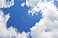 Sky and clouds background. Background made of blue sky framed by white clouds Stock Photos