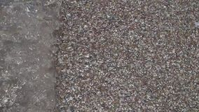 Background made of a closeup of a pile of pebbles. A wave on the sea carries away a wave of small stones and sand on the seashore stock footage