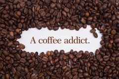 Background made of coffee beans in a heart shape with message `A coffee addict.` royalty free stock images