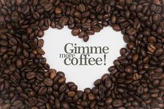 Background made of coffee beans in a heart shape with message `Gimme more coffee!` Royalty Free Stock Images