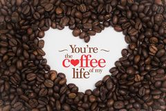 Background made of coffee beans in a heart shape with message `You`re the coffee of my life` Royalty Free Stock Images