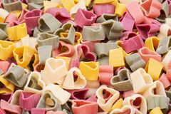 Background made of durum wheat semolina heart-shaped 5 flavors pasta with vegetables. Valentine`s Day stock images