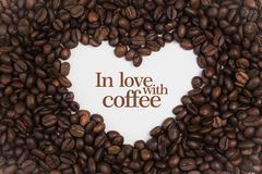 Background Made Of Coffee Beans In A Heart Shape With Message `In Love With Coffee` Royalty Free Stock Photos