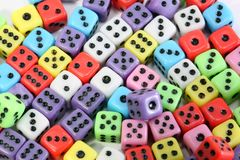 Many colored gaming dice with black dots. Background of many colored gaming dice with black dots royalty free stock photography