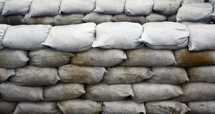 Background of many dirty sand bags for flood defense. Protective sandbag barricade for military use. Handsome tactical bunker stock images
