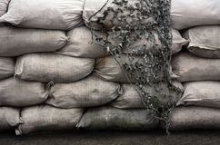Background of many dirty sand bags for flood defense. Protective sandbag barricade for military use. Handsome tactical bunker.  stock image