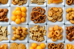 Background of many types of savory snacks in white square dishes. From above stock images