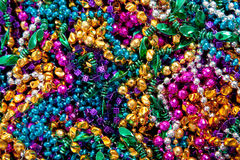 Background of mardi gras beads. A background of colorful mardi gras beads including gold, blue, green, pink and purple