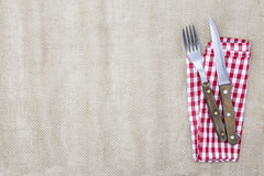 The background for the menu. Canvas tablecloth, fork,knife and napkin for steaks. Is used to create a menu for a steak house Stock Photos