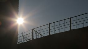Background. Metal fence on the back of the sun. Camera movement. Sun rays illuminate the fence. Background. Metal fence on the back of the sun. Camera movement stock video footage