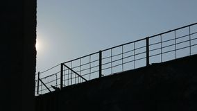 Background. Metal fence on the back of the sun. Camera movement. Sun rays illuminate the fence. Background. Metal fence on the back of the sun. Camera movement stock video