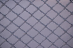 Background of metal mesh and snow. Background of metallic grid mesh in frost and snow Royalty Free Stock Image