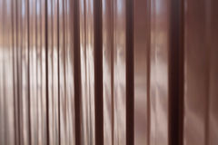 Background from metal profile sheet of chocolate color. Vertical waves are visible Royalty Free Stock Photo