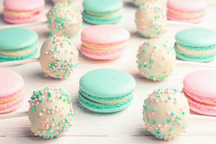 Background of mint and strawberry flavor macaroons and cake pops. Sweet background of mint and strawberry flavor macaroons and cake pops on sticks Stock Photos