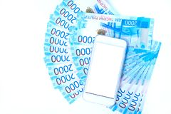 Background of money Russian banknotes currency roubleand and cell phone. in nominal value of two thousand. New tickets bank Russia. Close up. Rich concept royalty free stock image