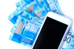Background of money Russian banknotes currency roubleand and cell phone. in nominal value of two thousand. New tickets bank Russia. Close up. Rich concept stock photography