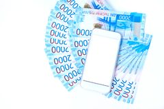 Background of money Russian banknotes currency roubleand and cell phone. in nominal value of two thousand. New tickets bank Russia. Close up. Rich concept stock images