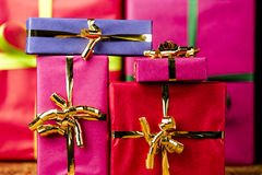 Background with Monochrome Gift Boxes. Plain presents in vibrant magenta, crimson and blue wrapping. Flattened space via tight framing. Background for any gift Stock Photos