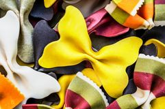Background from multi-colored pasta bows and striped. Selective focus. Stock Photos
