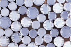Background of multiple sealed food cans. Or tins viewed from overhead in an assortment of sizes filling the frame in a food and nutrition concept Royalty Free Stock Images