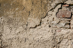 Background of natural cement plaster on the wall grey plain textured with cracks and brick in the upper right corner. Stock Photos