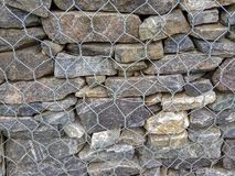 Background of natural gray stone tightened with mesh royalty free stock photo