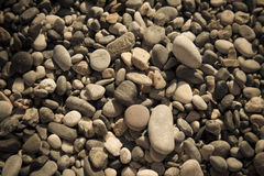 Background of natural pebble on a sea coast. Selective focus. To Royalty Free Stock Images
