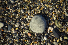 Background of natural pebble on a sea coast. Selective focus. To Stock Photography